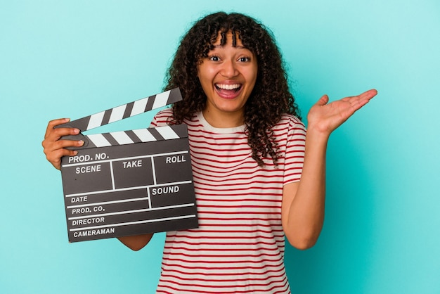 Young mixed race woman holding a clapperboard isolated on blue background receiving a pleasant surprise, excited and raising hands.