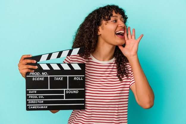 Young mixed race woman holding a clapperboard isolated on blue background shouting and holding palm near opened mouth.