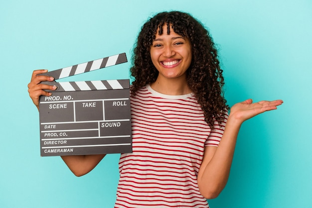 Young mixed race woman holding a clapperboard isolated on blue background showing a copy space on a palm and holding another hand on waist.
