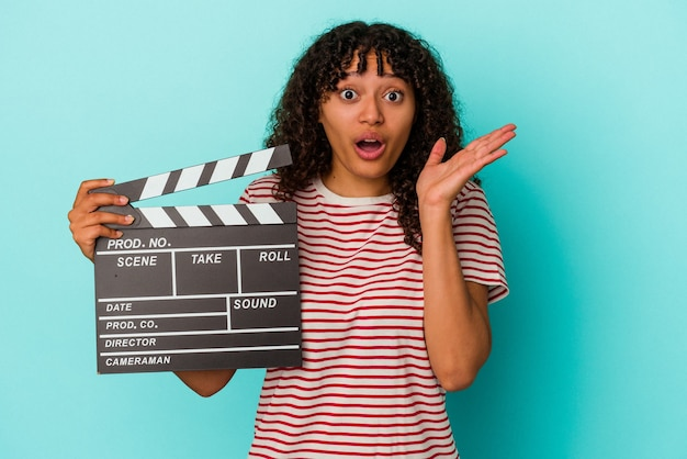 Young mixed race woman holding a clapperboard isolated on blue background surprised and shocked.