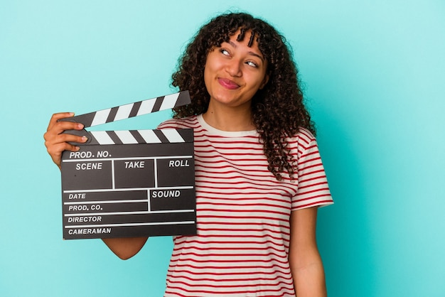 Young mixed race woman holding a clapperboard isolated on blue wall dreaming of achieving goals and purposes