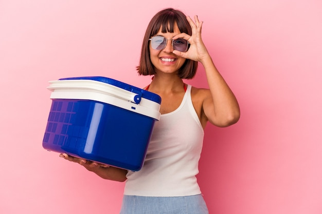 Young mixed race woman holding a cooler isolated on pink background excited keeping ok gesture on eye.
