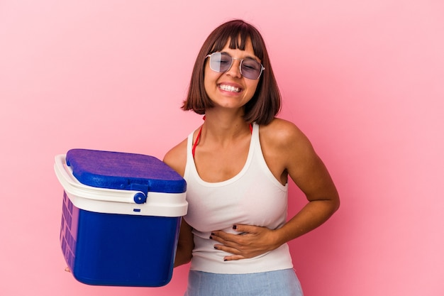 Young mixed race woman holding a cooler isolated on pink background laughing and having fun.