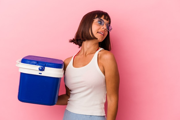 Young mixed race woman holding a cooler isolated on pink background looks aside smiling, cheerful and pleasant.