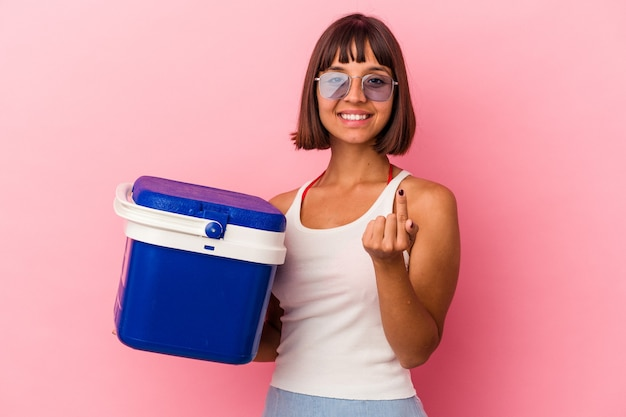 Young mixed race woman holding a cooler isolated on pink background pointing with finger at you as if inviting come closer.