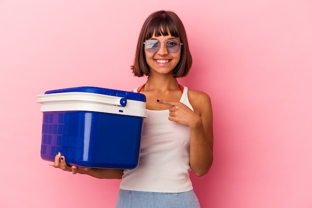 Young mixed race woman holding a cooler isolated on pink background smiling and pointing aside, showing something at blank space.