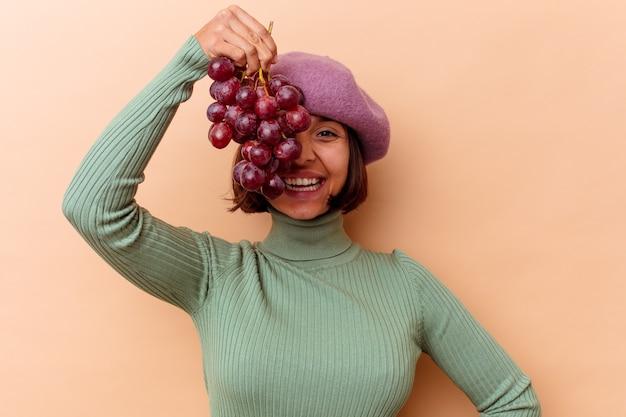 ベージュの背景で隔離のブドウを保持している若い混血の女性