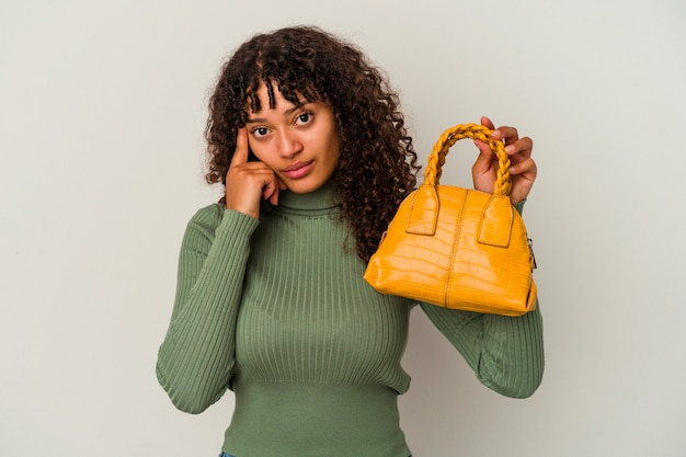 Young mixed race woman holding a handbag isolated on white wall pointing temple with finger, thinking, focused on a task.