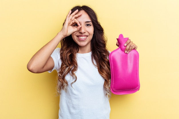 Young mixed race woman holding a hot bag isolated on yellow background excited keeping ok gesture on eye.