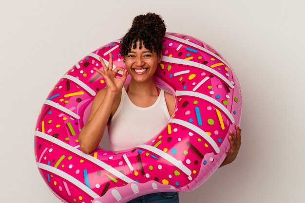 Young mixed race woman holding an inflatable air donut isolated on white background cheerful and confident showing ok gesture.
