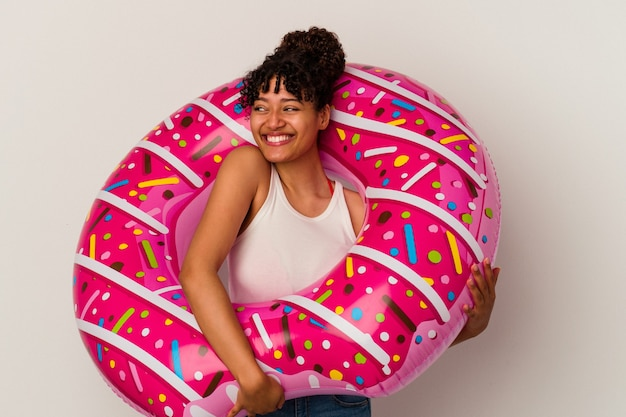 Young mixed race woman holding an inflatable air donut isolated on white background dreaming of achieving goals and purposes