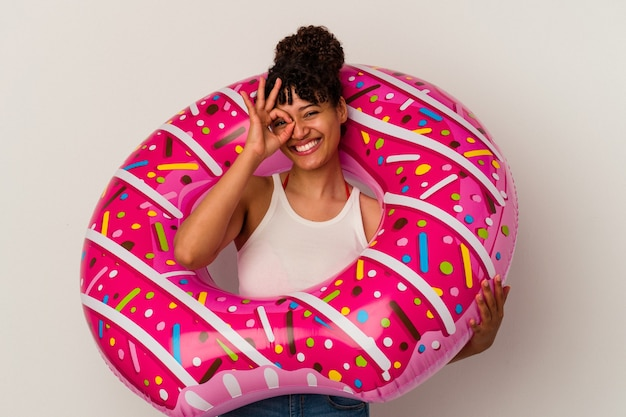 Young mixed race woman holding an inflatable air donut isolated on white background excited keeping ok gesture on eye.