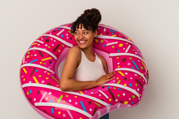 Young mixed race woman holding an inflatable air donut isolated on white background looks aside smiling, cheerful and pleasant.