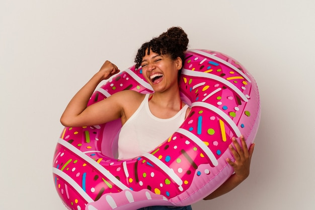 Young mixed race woman holding an inflatable air donut isolated on white background raising fist after a victory, winner concept.