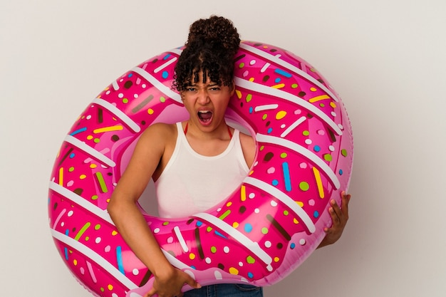Young mixed race woman holding an inflatable air donut isolated on white background screaming very angry and aggressive.