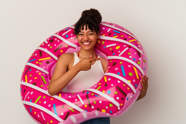 Young mixed race woman holding an inflatable air donut isolated on white background smiling and pointing aside, showing something at blank space.
