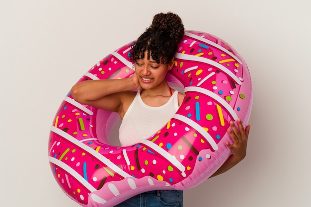 Young mixed race woman holding an inflatable air donut isolated on white background touching back of head, thinking and making a choice.