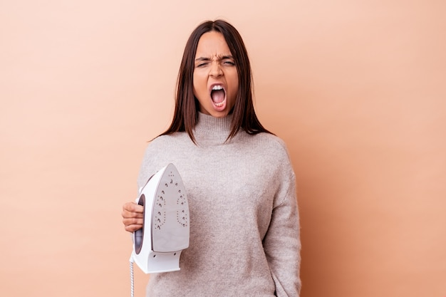 Young mixed race woman holding an iron isolated screaming very angry and aggressive.
