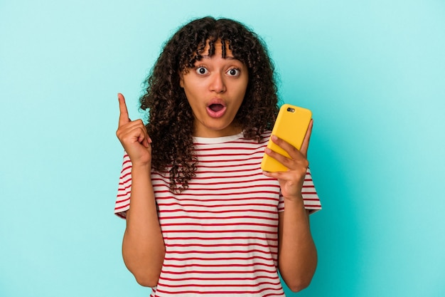 Young mixed race woman holding a mobile phone isolated on blue wall having an idea, inspiration concept.