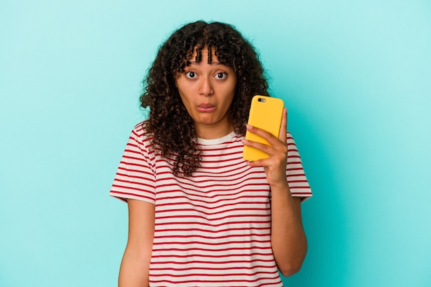 Young mixed race woman holding a mobile phone isolated on blue wall shrugs shoulders and open eyes confused.