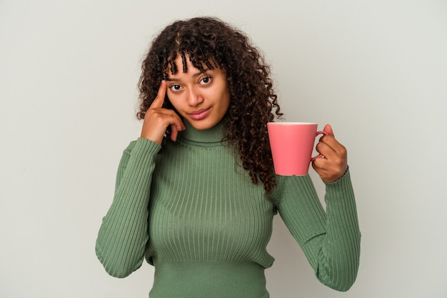 Young mixed race woman holding a mug isolated on white background pointing temple with finger, thinking, focused on a task.