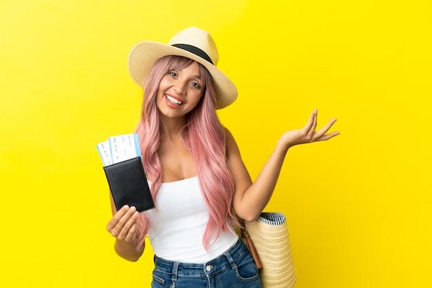 黄色の背景で隔離のパスポートとビーチバッグを保持している若い混血の女性は、来て招待するために手を横に伸ばします
