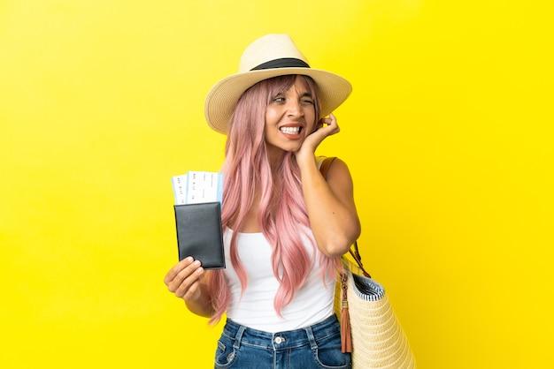 Молодая женщина смешанной расы, держащая паспорт и пляжную сумку на желтом фоне, разочарована и закрывает уши
