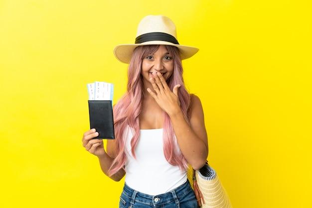 黄色の背景に分離されたパスポートとビーチバッグを保持している若い混血の女性幸せと笑顔の手で口を覆う