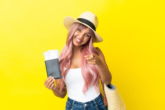 パスポートと幸せな表情で正面を指す黄色の背景に分離されたビーチバッグを保持している若い混血の女性