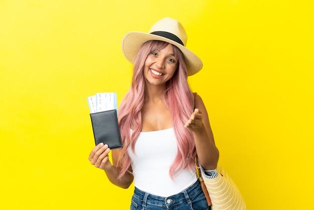 노란색 배경에 격리된 여권과 해변 가방을 들고 좋은 거래를 성사시키기 위해 악수하는 젊은 혼혈 여성