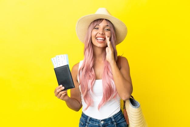 口を大きく開いて叫んで黄色の背景に分離されたパスポートとビーチバッグを保持している若い混血の女性