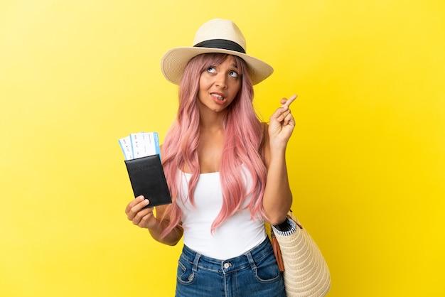 Молодая женщина смешанной расы держит паспорт и пляжную сумку на желтом фоне со скрещенными пальцами и желает всего наилучшего
