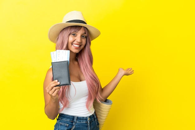 Young mixed race woman holding passport and beach bag isolated on yellow background extending hands to the side for inviting to come