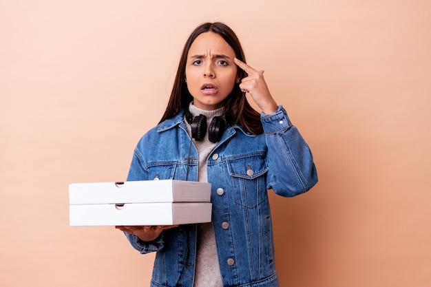 Young mixed race woman holding a pizza isolated showing a disappointment gesture with forefinger.