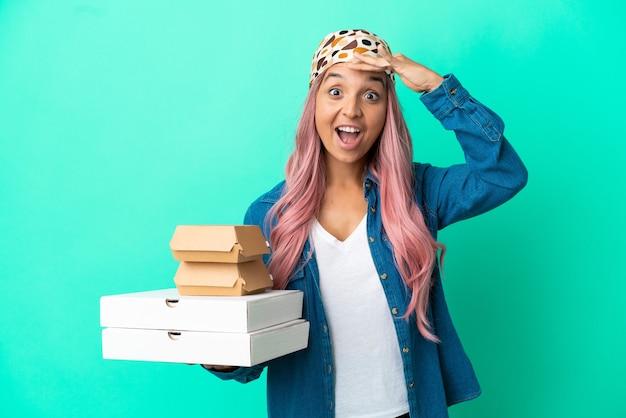 Молодая женщина смешанной расы, держащая пиццу и гамбургеры, изолированные на зеленом фоне, делает неожиданный жест, глядя в сторону