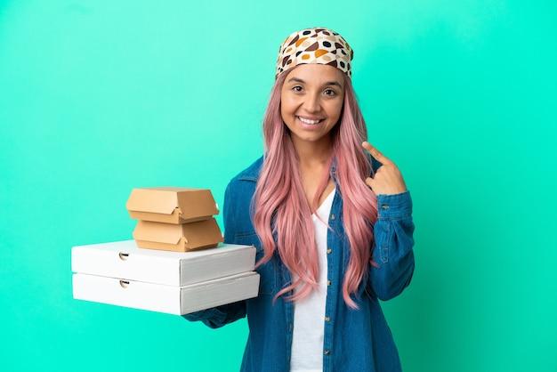 親指を立てるジェスチャーを与える緑の背景に分離されたピザやハンバーガーを保持している若い混血の女性