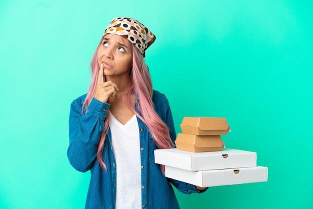 Молодая женщина смешанной расы, держащая пиццу и гамбургеры, изолированные на зеленом фоне, сомневаясь, глядя вверх