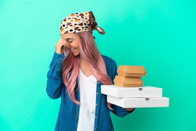 Молодая женщина смешанной расы, держащая пиццу и гамбургеры, изолированные на зеленом фоне смеясь