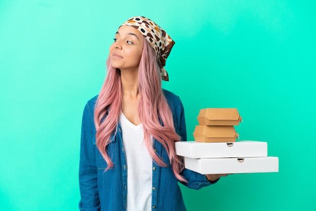 Молодая женщина смешанной расы, держащая пиццу и гамбургеры, изолированные на зеленом фоне, глядя в сторону и улыбаясь