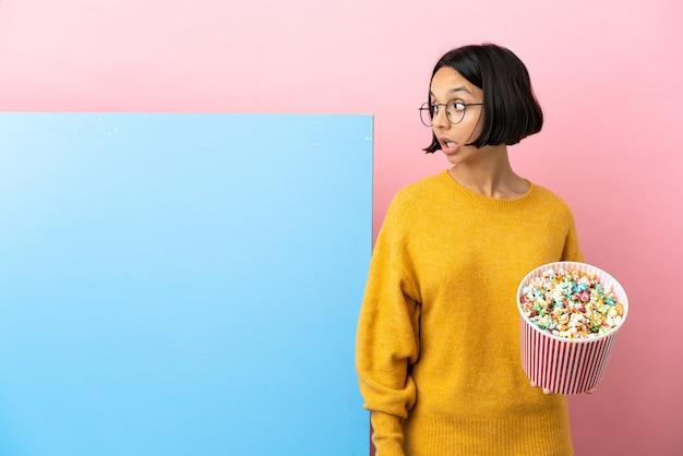 Молодая женщина смешанной расы, держащая попкорн с большим баннером на изолированном фоне, делает неожиданный жест, глядя в сторону