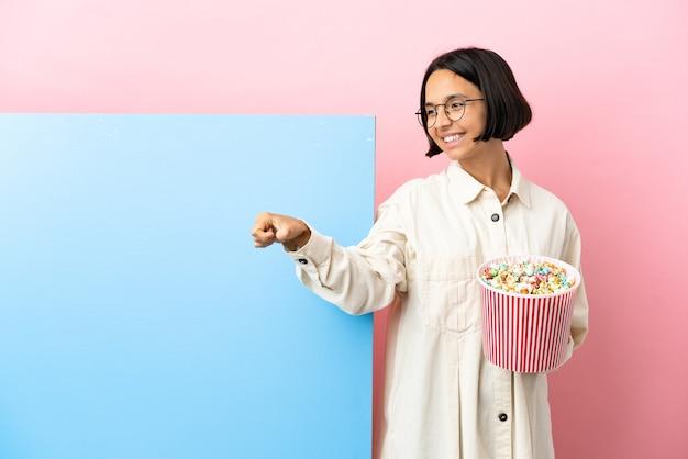 Молодая женщина смешанной расы, держащая попкорн с большим баннером на изолированном фоне, показывая жест рукой вверх