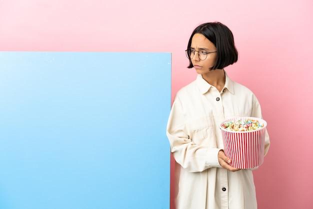 Молодая женщина смешанной расы, держащая попкорн с большим баннером на изолированном фоне, сомневающаяся, глядя в сторону