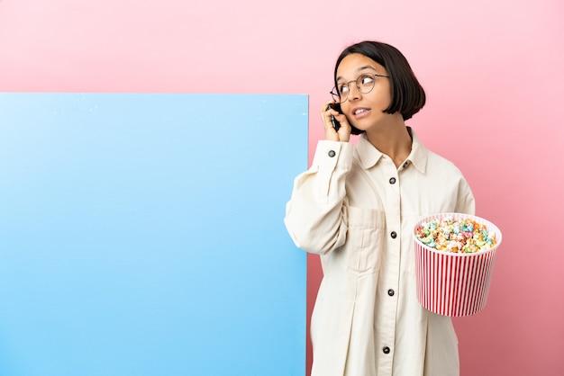 고립된 배경 위에 팝콘을 들고 있는 젊은 혼혈 여성