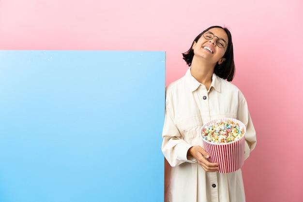 Молодая женщина смешанной расы, держащая попкорн с большим баннером на изолированном фоне, смеясь