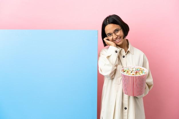 笑っている孤立した背景の上に大きなバナーとポップコーンを保持している若い混血の女性