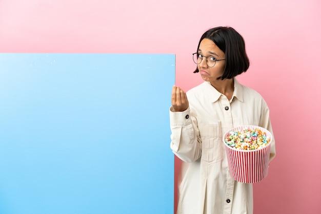 이탈리아 제스처를 만드는 고립 된 배경 위에 큰 배너와 함께 팝콘을 들고 젊은 혼혈 여성