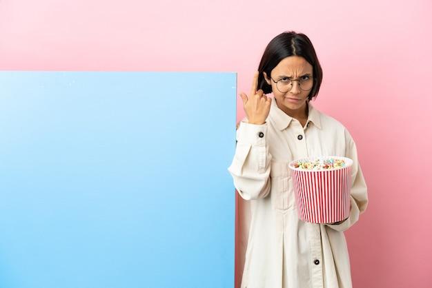 Молодая женщина смешанной расы держит попкорн с большим баннером на изолированном фоне, делая жест безумия, положив палец на голову