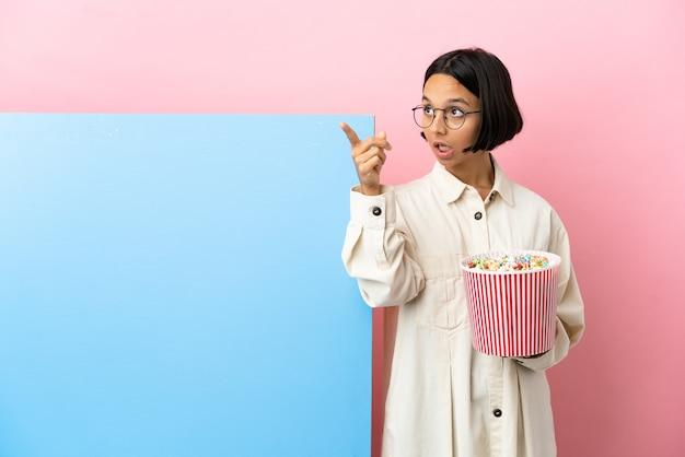 Молодая женщина смешанной расы держит попкорн с большим баннером на изолированном фоне, указывая в сторону