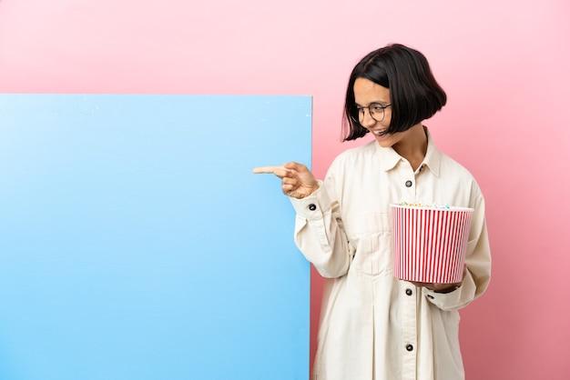 横に指を指し、製品を提示する孤立した背景の上に大きなバナーでポップコーンを保持している若い混血の女性