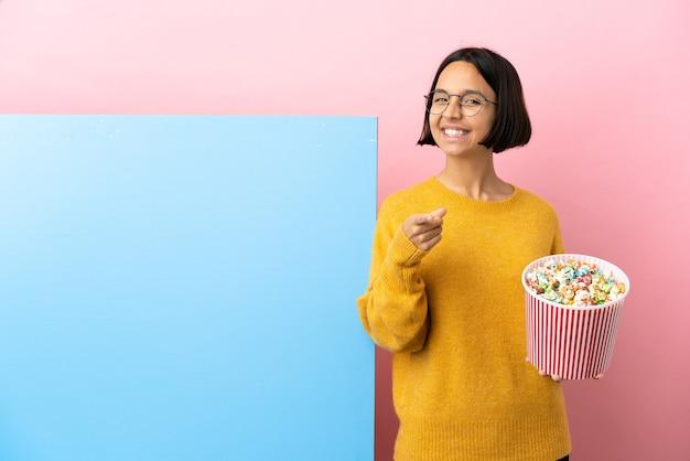 幸せな表情で正面を指している孤立した背景の上に大きなバナーとポップコーンを保持している若い混血の女性